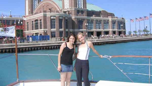 Two teenage girls posing for a photo on a charter yacht. An old building is in the background