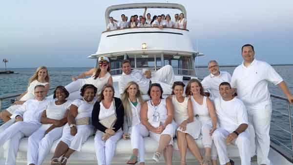 A group of men an women dressed in white outfits on the top deck of a charter yacht in Chicago IL