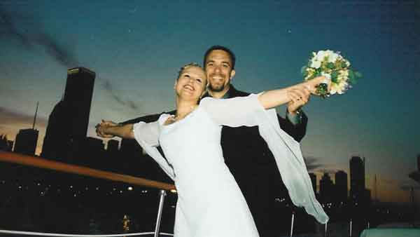 A wedding couple posing like Leonardo di Caprio and Claire Danes on a Chicago yacht charter like Titanic