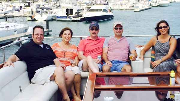 Five people posing for a photo on the top deck of a charter yacht in Chicago IL