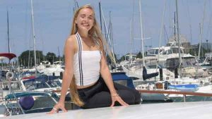 A blonde haired teen ager dressed like Tifa from Final Fantasy poses for a photo on a charter yacht