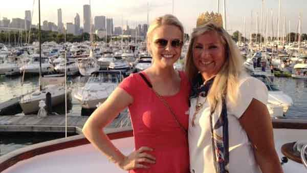 Two women on the deck of a charter yacht in Chicago IL, the background has many yachts