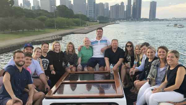 A group of people on the top deck of a charter yacht overseeing Chicago IL