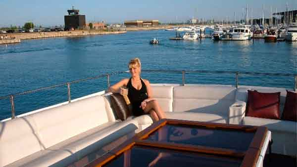 A woman sits alone posing on the top deck of the Sophisticated Lady yacht charter