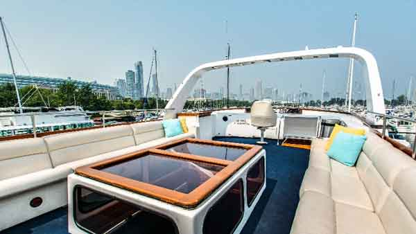 Top deck with a glass table on the Sophisticated Lady yacht charter